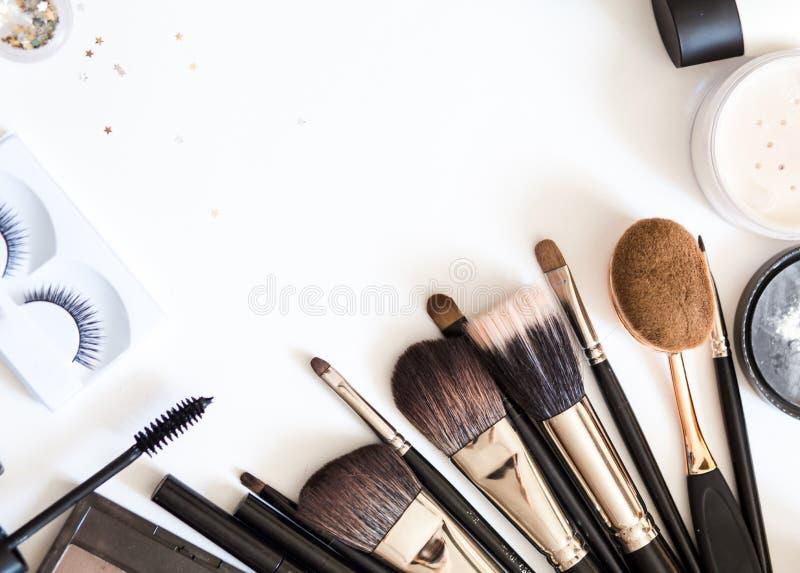 Les brosses pour les cosmétiques décoratifs pour composent sur la vue supérieure de fond blanc flatlay images stock