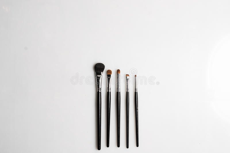 Les brosses pour le maquillage sur le fond blanc ont photographié d'en haut photographie stock libre de droits