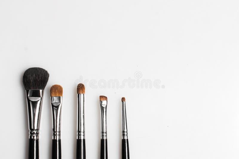 Les brosses pour le maquillage sur le fond blanc ont photographié d'en haut photos stock