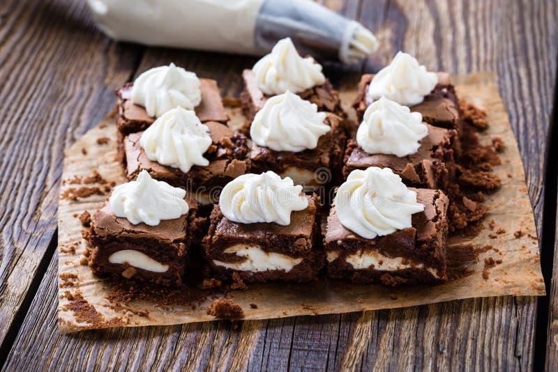 Les 'brownie' de gâteau au fromage avec le fromage fondu ont tourbillonné givrage photo libre de droits