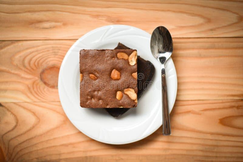 Les 'brownie' durcissent sur la tranche de gâteau de table/chocolat avec l'écrou dans le plat avec la cuillère sur en bois photos libres de droits