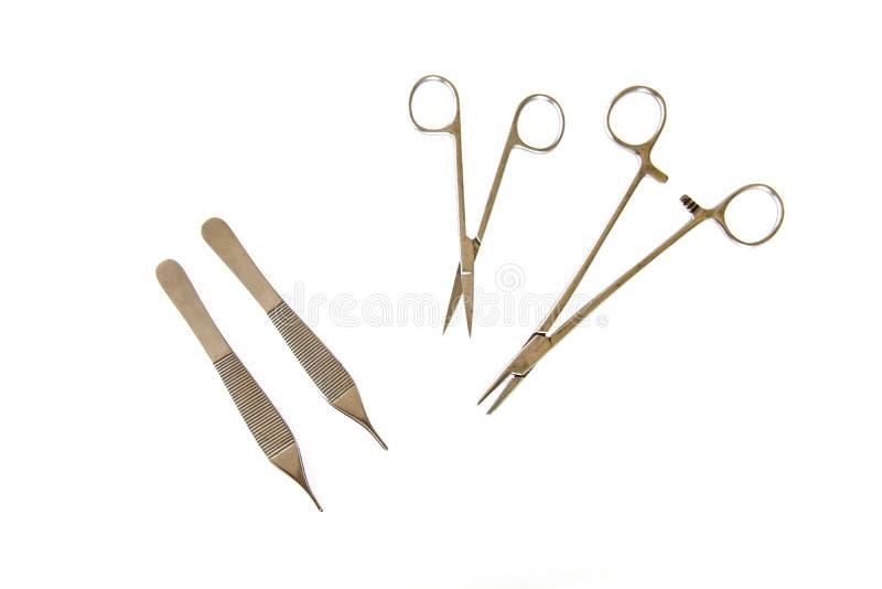 Les brucelles d'instruments chirurgicaux, pinces, maintiennent la lame, le scalpel, ciseaux sur une table blanche images libres de droits