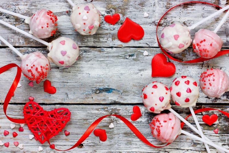 Les bruits rouges de gâteau de velours couverts en chocolat blanc décoré du sucre rouge et rose arrose pour le Saint Valentin photos libres de droits
