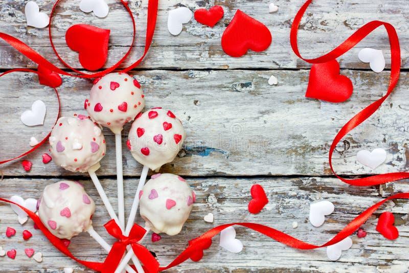 Les bruits rouges de gâteau de velours couverts en chocolat blanc décoré du sucre rouge et rose arrose pour le Saint Valentin photos stock