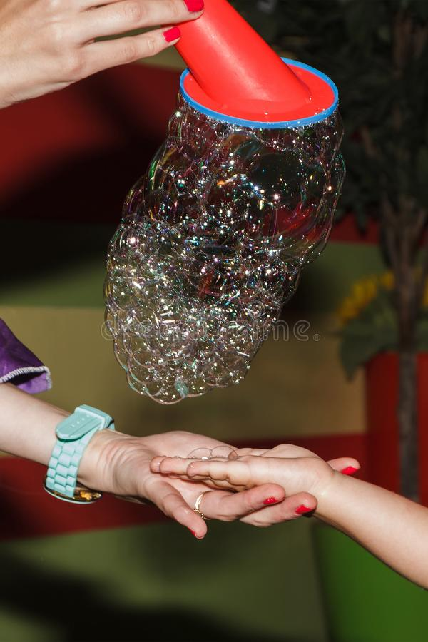 Les bulles de savon du tube tombe sur la main d'un enfant, les vacances des enfants de concept photo libre de droits