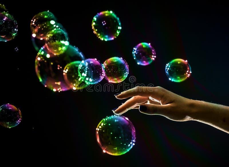 Les bulles de savon transparentes et iridescentes d'isolement sur le noir image stock
