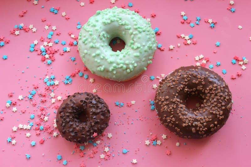 Les butées toriques colorées dans le lustre sur le fond rose avec multicolore arrose des étoiles de sucre image stock