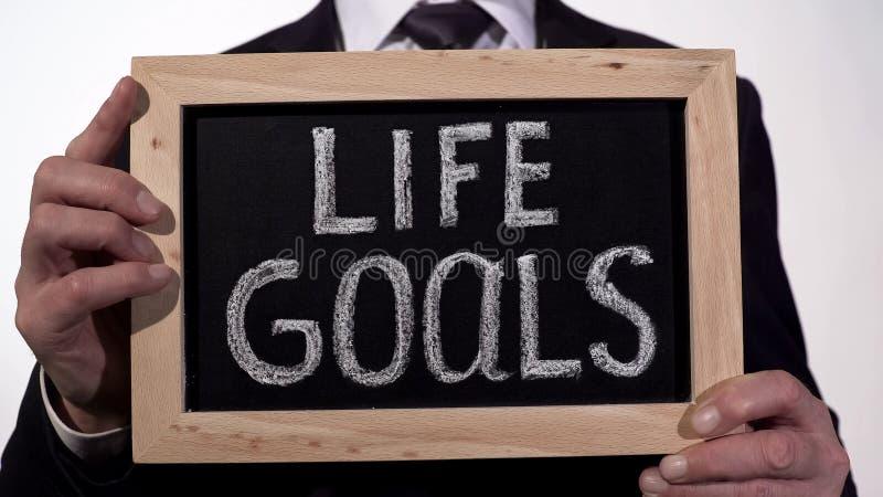 Les buts de la vie écrits sur le tableau noir dans des mains d'homme d'affaires, succès incline, motivation photographie stock libre de droits