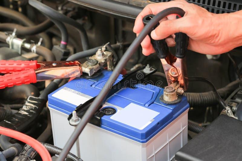 Les câbles de pullover de batterie d'utilisations de mécanicien de voiture chargent une batterie morte photos stock