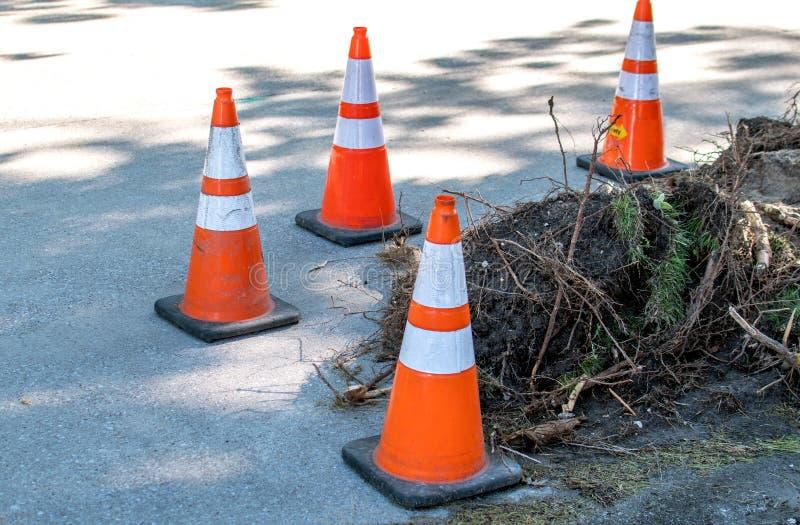 Les cônes de sécurité gardent un trou ouvert sur une route locale images stock