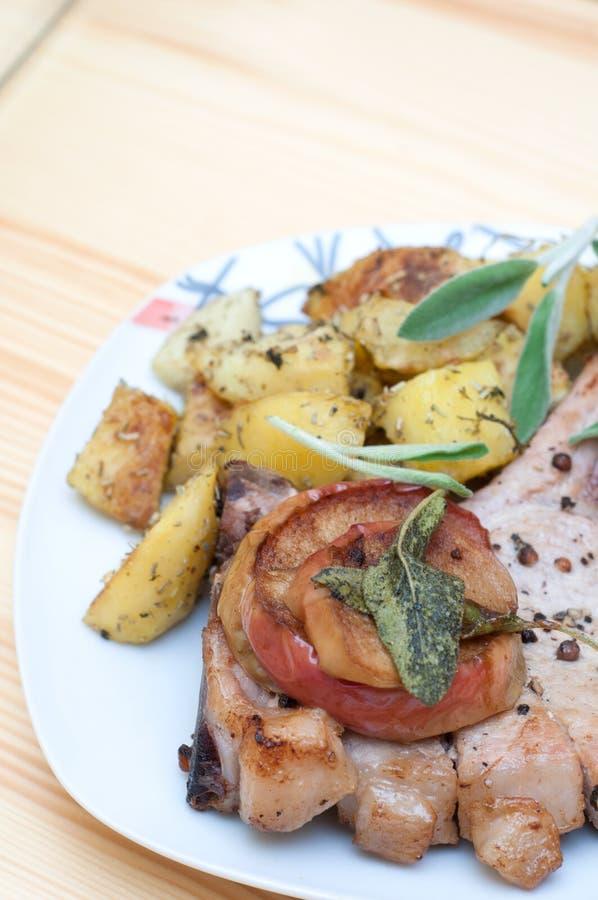 Les côtelettes de porc avec des pommes et le four ont rôti des pommes de terre photographie stock