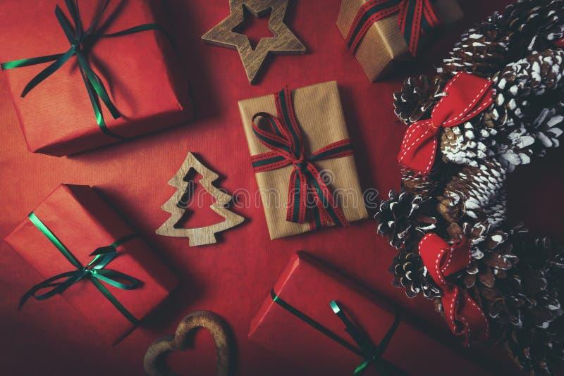 Les cadeaux de Noël et les couronnes de l'avènement sur fond de papier rouge photos libres de droits