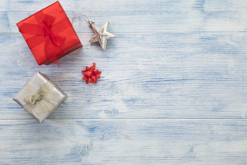 Les cadeaux de Noël, l'étoile d'argent et l'arc en ruban Arrière-plan rustique avec espace de copie photos stock