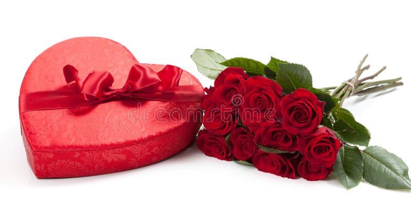 Les cadeaux de Valentine comprenant un bouquet des roses et du coeur de sucrerie photos stock