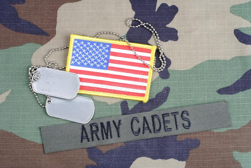 Les CADETS de l'ARMÉE AMÉRICAINE s'embranchent bande, correction de drapeau et les étiquettes de chien sur la région boisée camou photo libre de droits