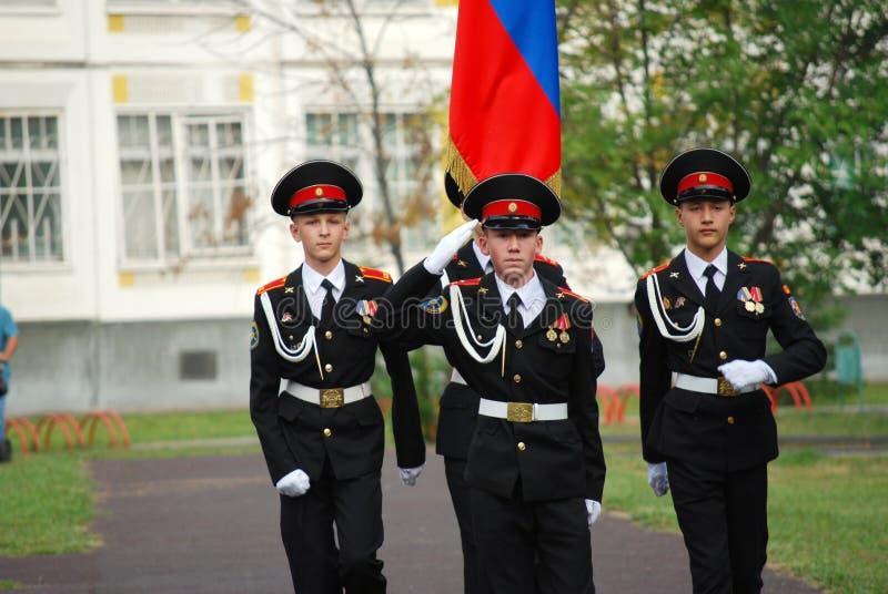 Les cadets marchent avec une bannière sur une règle de matin avant école sur la défilé-terre Étudiants d'école photos stock