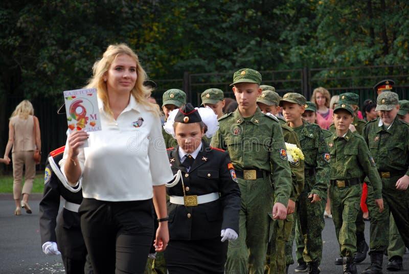 Les cadets marchent avec une bannière sur une règle de matin avant école sur la défilé-terre Étudiants d'école photographie stock