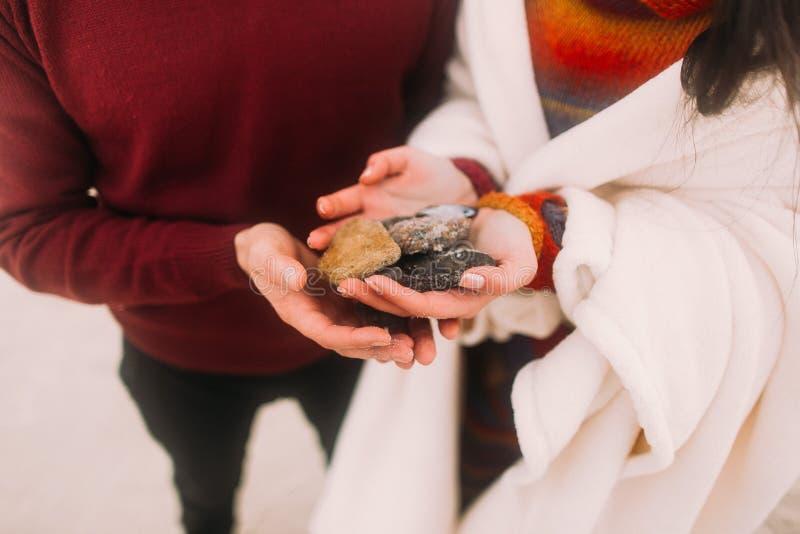 Les cailloux colorés de mer sur les mains du couple se ferment  Jeunes couples heureux à la plage d'hiver enveloppée dans la couv images stock