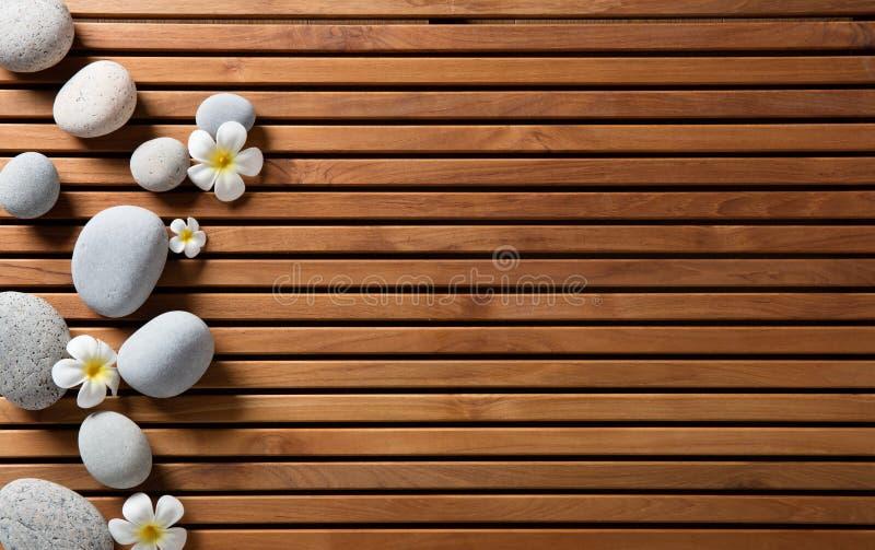 Les cailloux de zen et les fleurs de station thermale ont placé sur le conseil en bois de hammam images libres de droits
