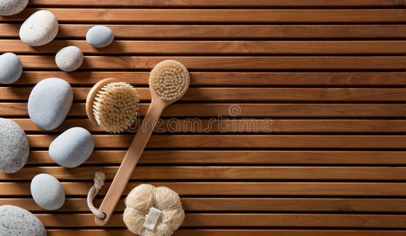 Les cailloux ont placé sur le panneau en bois de bain turc avec des brosses de corps photos stock