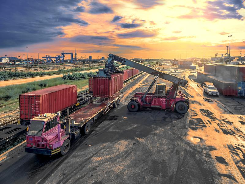 Les camions de grue soulèvent le récipient dans le port de transport d'entrepôt photo libre de droits