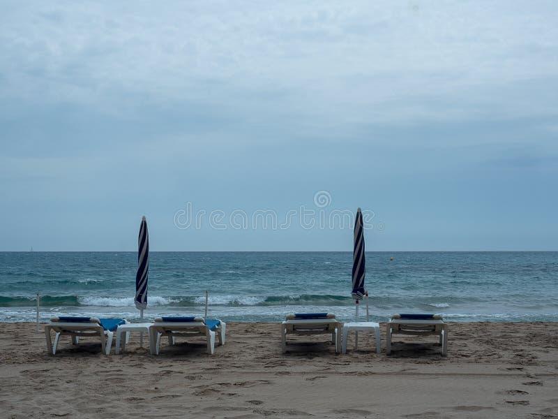 Les canapés et les parapluies de Sun se sont fermés sur le bord de la mer photo stock
