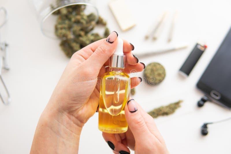 Les cannabis CBD d'huile dans la main de femmes de pipette, se ferment, le produit de mauvaise herbe, extrait de marijuana sur le photo libre de droits