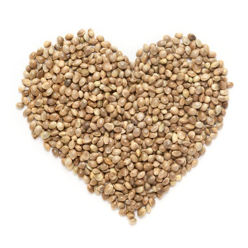 Les cannabis organiques de graines de chanvre sativa au coeur forment photographie stock libre de droits