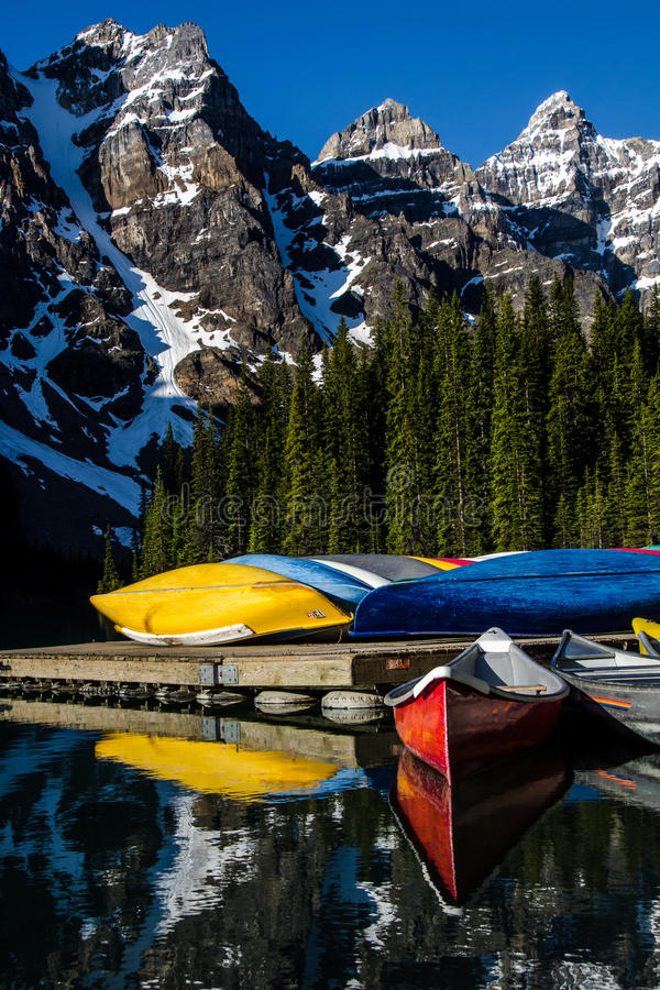 Les canoës lumineux au lac de moraine avec la neige ont couvert les montagnes rocheuses à l'arrière-plan image stock