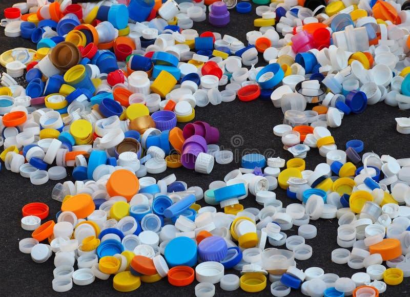 Les capsules et d'autres types de chapeaux en plastique ont dispersé sur une surface noire photo libre de droits