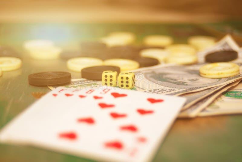 Les cartes de jeu, les matrices, les puces et l'argent sont sur la table de jeu de casino photos stock