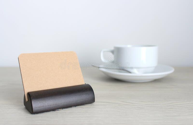 Les cartes de visite professionnelle de visite et la tasse de café vides sur le bureau en bois ajournent des WI photos stock