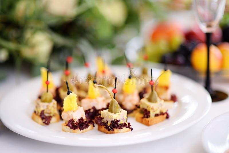 Les casse-croûte délicieux de canape avec l'écrimage d'ananas et de câpres ont servi sur une réception de partie ou de mariage photos libres de droits