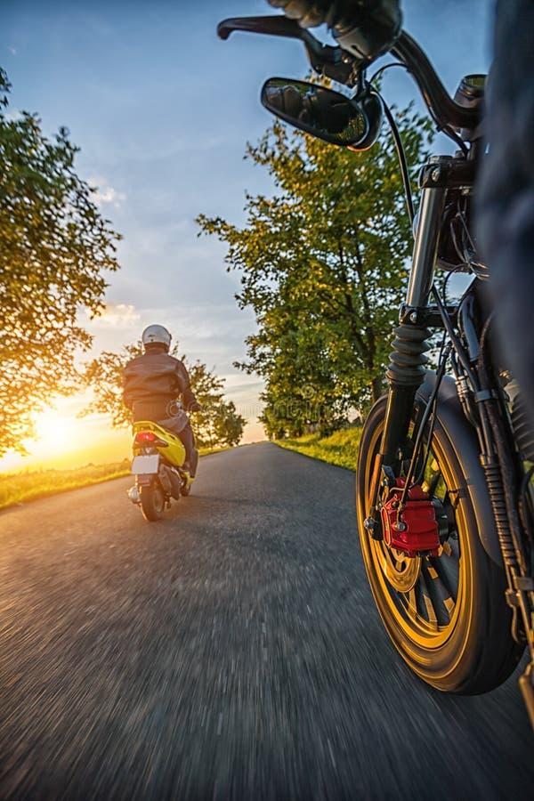 Les cavaliers de motocyclette conduisant vers le beau coucher du soleil s'allument sur vide image libre de droits