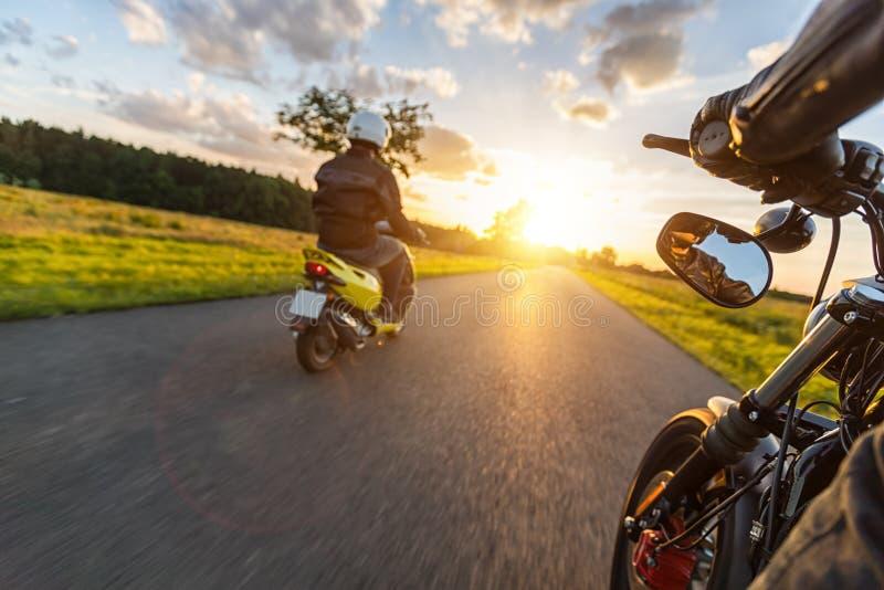 Les cavaliers de motocyclette conduisant vers le beau coucher du soleil s'allument sur vide images libres de droits