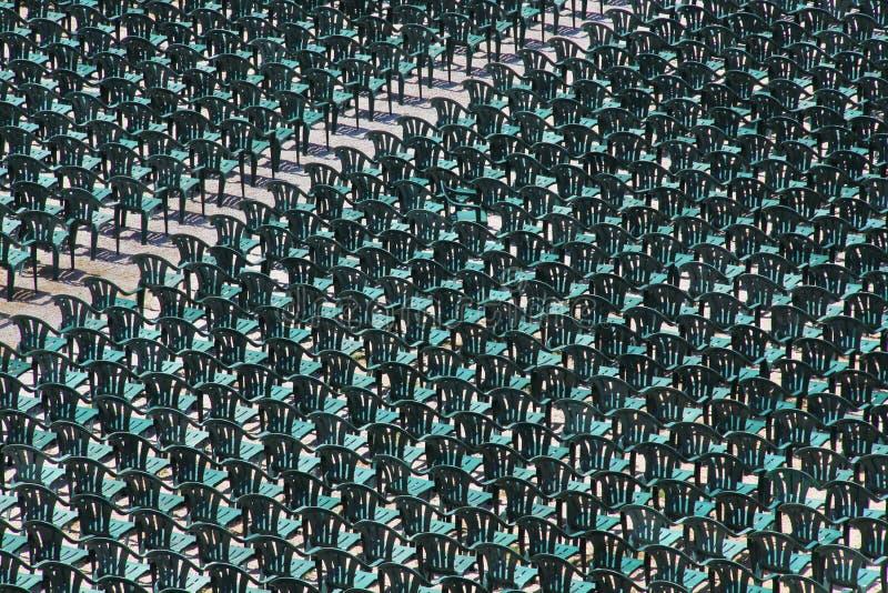 Les centaines de chaises vertes en plastique ont arrangé dans une rangée photos stock