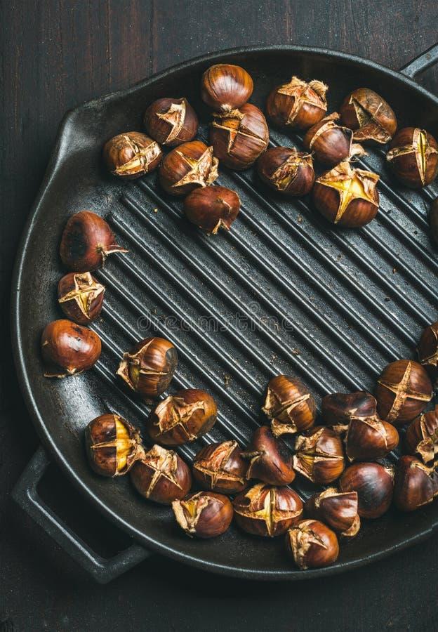 Les châtaignes rôties en grillant la casserole au-dessus de l'obscurité ont roussi le fond en bois image libre de droits