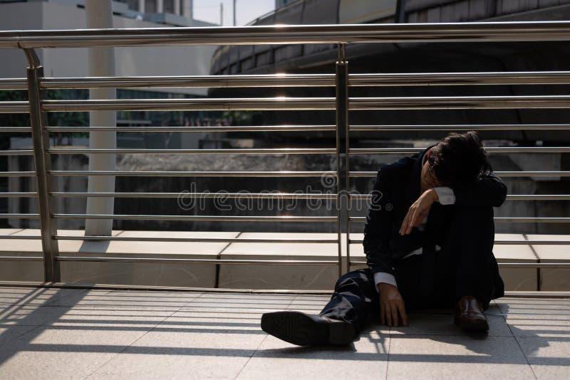 Les chômeurs ont soumis à une contrainte le jeune homme asiatique d'affaires s'asseyant sur le plancher dehors Concept d'échec et photographie stock