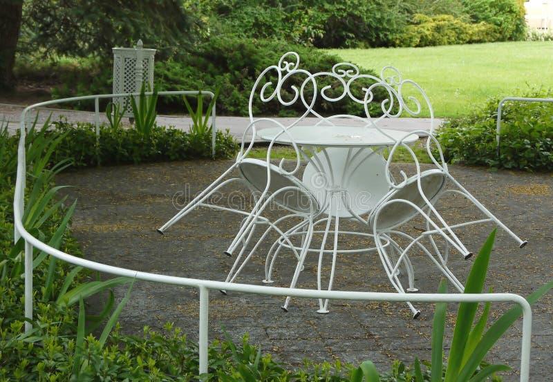 Les chaises blanches ornementées de parc de fer se sont penchées à la table images stock
