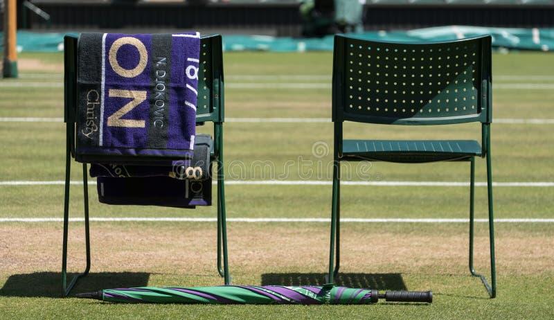 Les chaises de ` de joueurs avec la serviette ont replié le dos, et un parapluie vert et pourpre au sol La serviette a le nom Djo photos stock