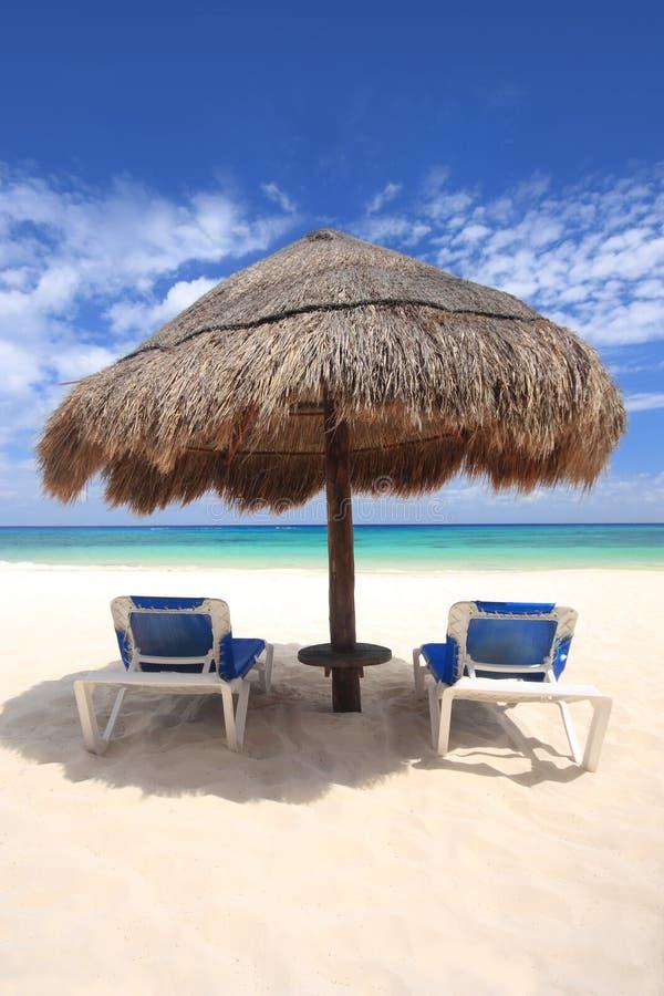 Les chaises de plage sous le palapa ont couvert la hutte de chaume photos libres de droits