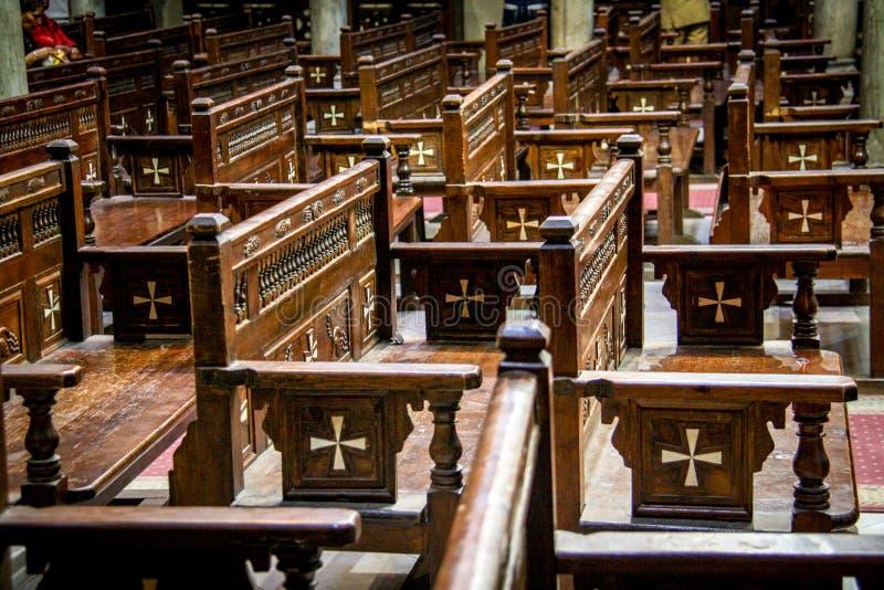 Les chaises en bois ont orné avec des croix à l'intérieur de l'église accrochante au Caire images libres de droits