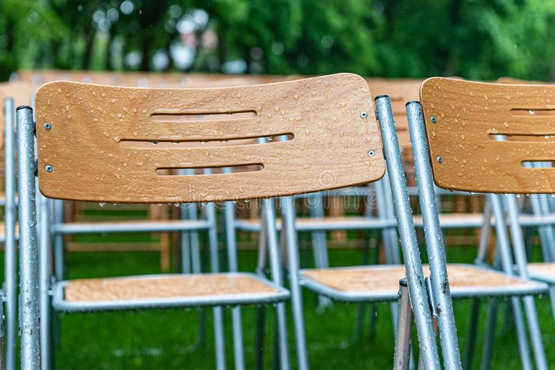 Les chaises en bois se tiennent extérieures en parc sous la pluie Amphithéâtre vide, herbe verte, waterdrops, plan rapproché photos libres de droits