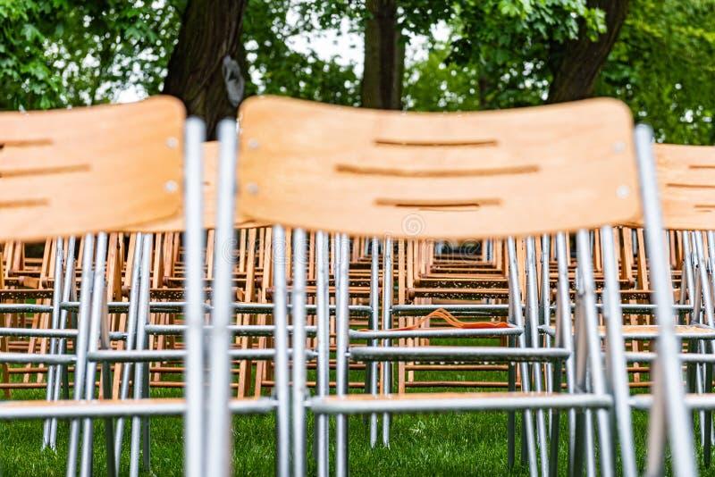 Les chaises en bois se tiennent extérieures en parc sous la pluie Amphithéâtre vide, herbe verte, waterdrops, plan rapproché images stock