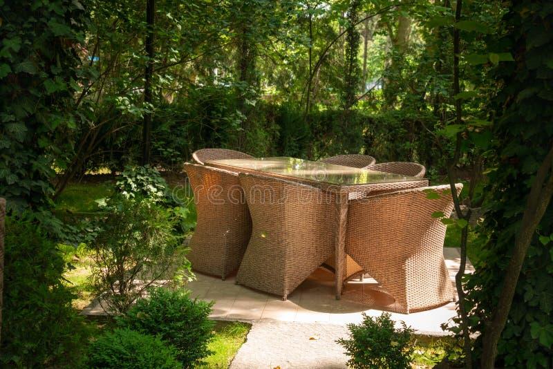 Les chaises en osier et la table sont dans le jardin près des arbres image stock