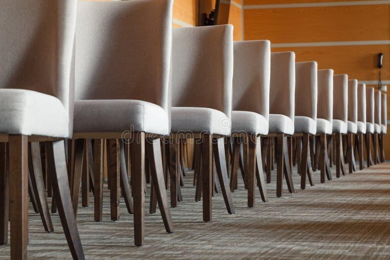 Les chaises grises de textile avec les jambes en bois brunes se tiennent dans un l droit images libres de droits