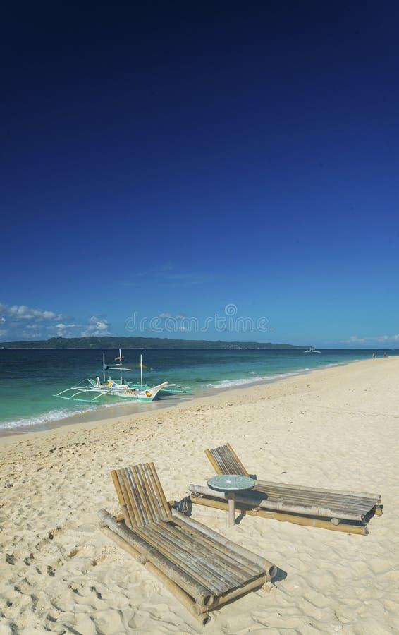 Les chaises longues et le bateau traditionnel sur le puka échouent à boracay phil photos stock