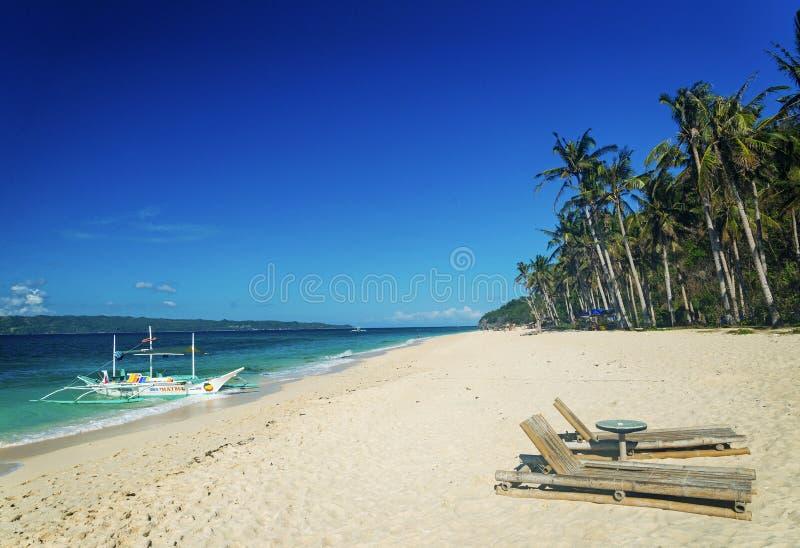 Les chaises longues et le bateau traditionnel sur le puka échouent à boracay phil photographie stock libre de droits