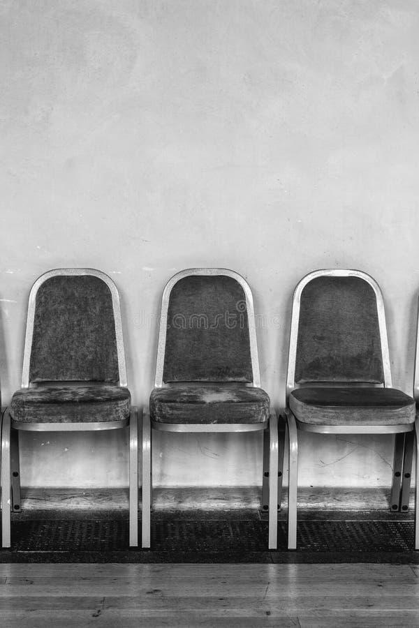 Les chaises ont aligné contre un mur dans un refuge dans le noir et le wh image libre de droits