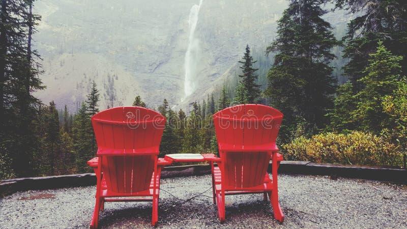 Les chaises rouges célèbres faisant face à Takakkaw tombe dans le Canada photographie stock libre de droits